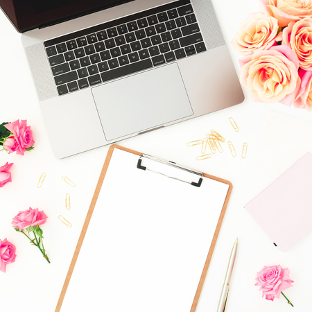 Laptop, clipboard, roses flowers and accessories on white background. Flat lay. Top view.