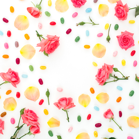 Frame of roses flowers and petals with bright sugar candy on white background. Flat lay, top view.