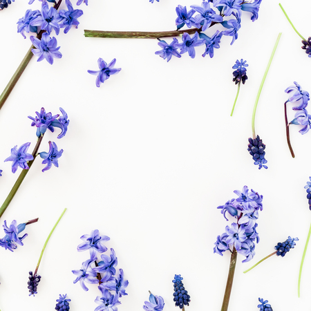 Frame of blue flowers and petals, floral pattern on white background. Flat lay, top view.
