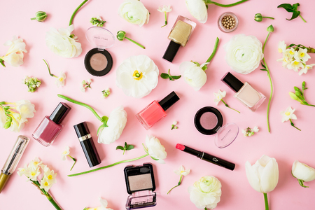 Beauty female blogger composition with flowers, cosmetics and accessory on pink background. Top view. Flat lay.