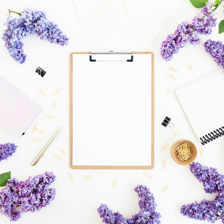 Feminine composition with clipboard, diary, lilac flowers and accessories on white background. Flat lay