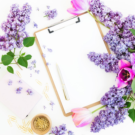 Composition with clipboard, lilac flowers and accessories on white background. Spring time. Flat lay Stock Photo