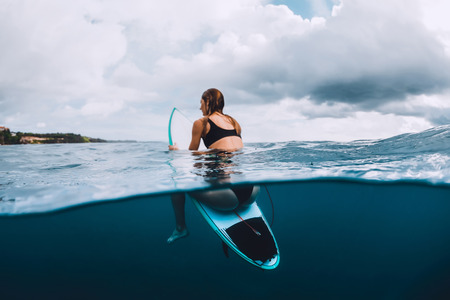 Attractive young surf girl sit at surfboard in blue ocean