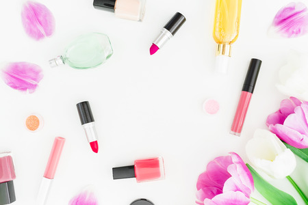 Frame made of tulips flowers and cosmetics, lipstick, nail polish on white background. Top view. Flat lay Stock Photo