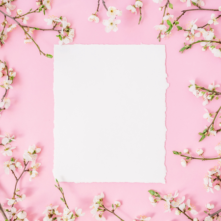 Floral frame with white flowers and card on pastel pink background. Flat lay, top view.