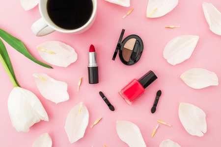 Composition with tulips flowers, coffee cup and cosmetics on pink background. Top view. Flat lay. Standard-Bild