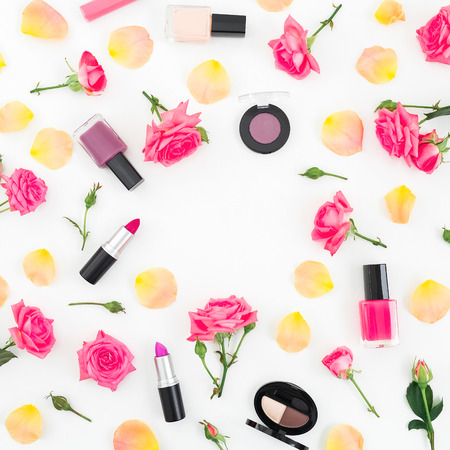 Flat lay frame composition with orange roses flowers and cosmetics on white background.Top view. Stock Photo