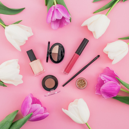 Beauty composition with tulips and cosmetics on pink background. Top view. Flat lay.