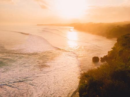 Vista aerea delle onde tempestose all'alba calda e alla spiaggia sabbiosa
