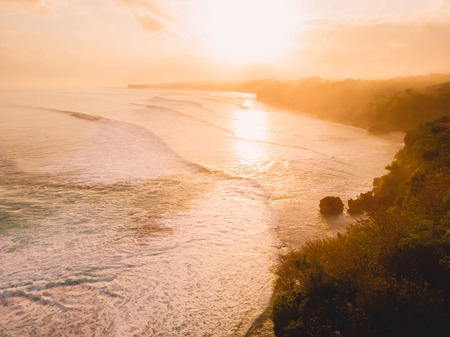 Vue aérienne des vagues orageuses au lever du soleil chaud et à la plage de sable