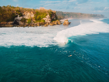 Aerial view with surfers and barrel blue wave in ocean, Padang Padang