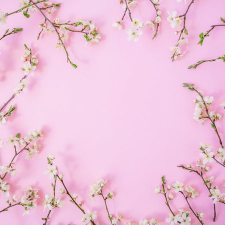 Floral frame with spring flowers on pink background. Flat lay, top view Stock Photo