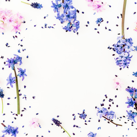 Pattern made of blue or pink flowers and petals on white background. Flat lay, top view.