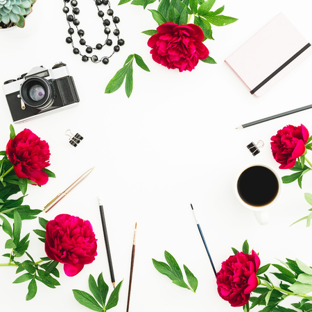 Frame composition. Blogger or freelancer workspace desk with retro camera, peonies and accessories on white background. Flat lay, top view.