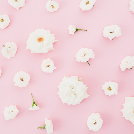 Pattern with white roses on pastel pink background. Flat lay Stock Photo
