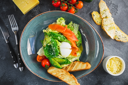 Salad with eggs, salmon fish, avocado, tomatoes and grilled toast on grey background. Flat lay Stock Photo