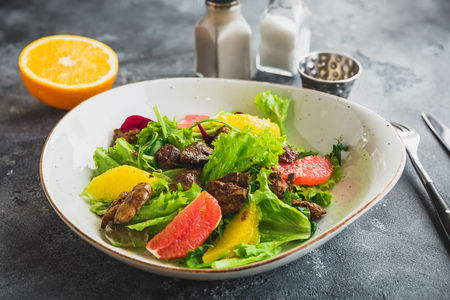Tasty salad with citrus, lettuce and chicken liver Stock Photo