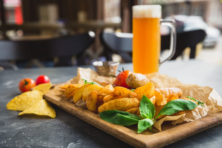 BBQ sausages with fried potatoes, tomato on wooden plate and glass of alcoholic beer Stock Photo