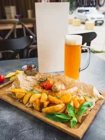 Grilled sausages with fried potatoes and pickled tomato on wooden board and glass of beer Stock Photo