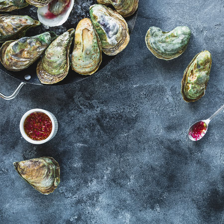 Raw ocean oysters on dark table. Flat lay. Top view. Food background Stock Photo