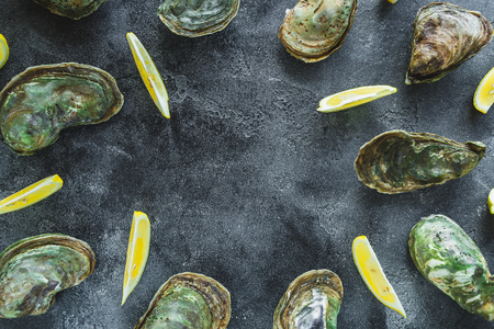 Oysters with limes on dark background. Delicious sea food composition. Flat lay