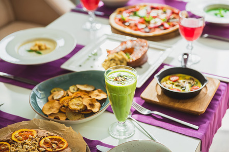 Table in cafe with vegetarian dishes - pizza, salads, pie with citrus and drinks. Stock Photo