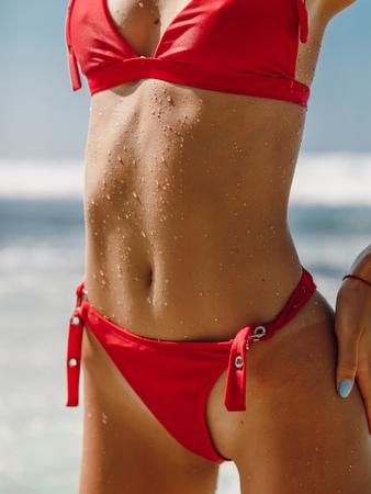Sexy body of young woman in red bikini at ocean beach in Bali Stock Photo