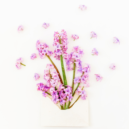 Beauty blog concept. Bouquet of pink flowers, petals and envelope on white background. Flat lay, top view.