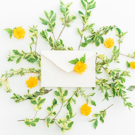 Yellow flowers and envelope on white background. Flat lay, Top view. Floral spring background
