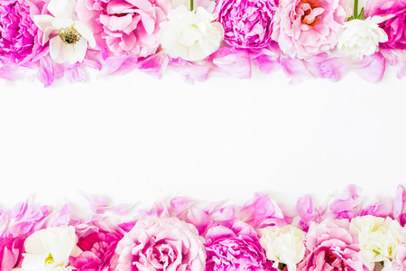 Frame of pink ranunculus flowers and roses on white background. Floral lifestyle composition. Flat lay