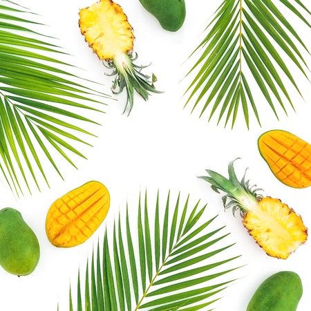 Tropic pattern of pineapple and mango fruits with palm leaves on white background. Flat lay, top view Stock Photo