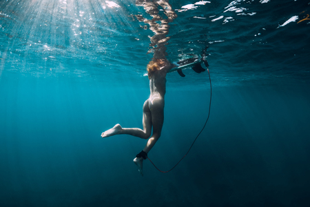 Naked surfer woman relaxing in sea. Nude woman with surfboard, underwater