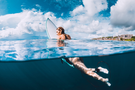 Naked woman with surfboard in sea Stock Photo