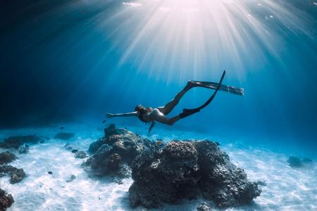 Femme apnéiste glisse avec des palmes sur une mer de sable. Plongée en apnée dans l'océan bleu