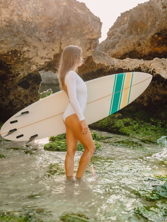 Surfer girl with surfboard in ocean.