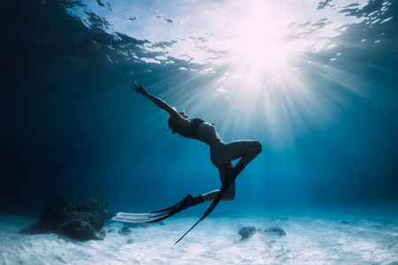 Woman freediver over sandy sea with fins. Freediving in ocean
