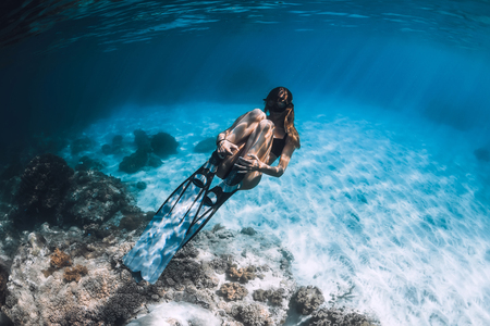 Woman freediver with fins swim in blue sea. Underwater in ocean 写真素材