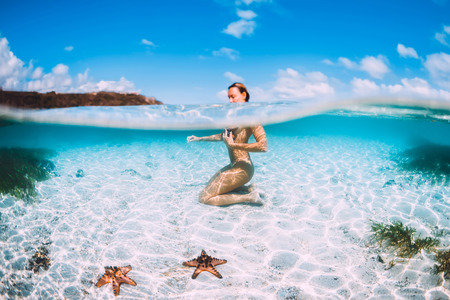 Naked woman swim in blue ocean with starfish, underwater in tropical sea Standard-Bild