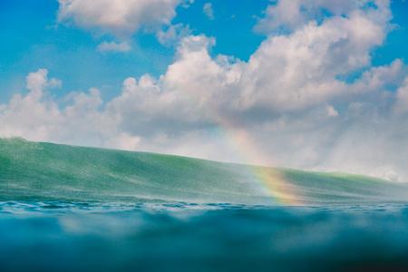 Rainbow by big wave in ocean. Breaking wave, drops and rainbow Banco de Imagens