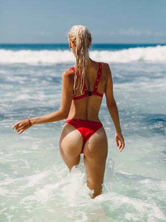 Mujer joven atractiva en bikini relajarse en la playa tropical de Bali. Modelo con océano Foto de archivo