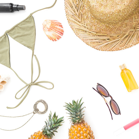 Frame with pineapple, sun glasses, straw hat and bikini swimwear on white background. Flat lay, top view.