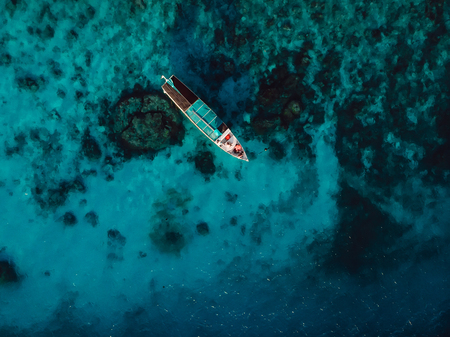Tour boat at the in blue ocean on Gili island. Aerial view.
