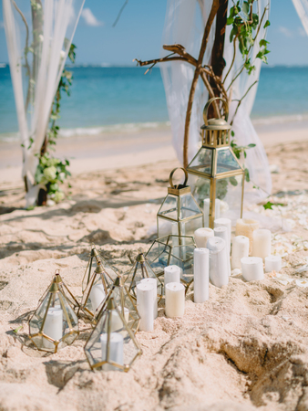 Decorations of wedding arch with white flowers and candles at beach 写真素材