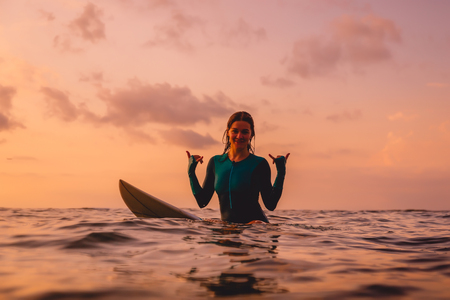 Smiling surfer woman sit on a surfboard in ocean. Surfing at sunset 写真素材