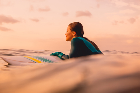 Attractive surf girl with perfect body on surfboard in ocean. Surfing at sunset time