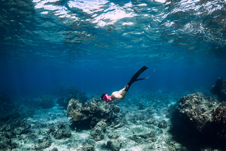 Young woman freediver with fins dive underwater ocean 写真素材