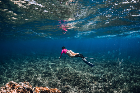 Woman freediver glides with fins over coral reef. Freediving in blue ocean