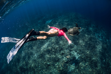 Young woman freediver with fins swim underwater with sea turtle.