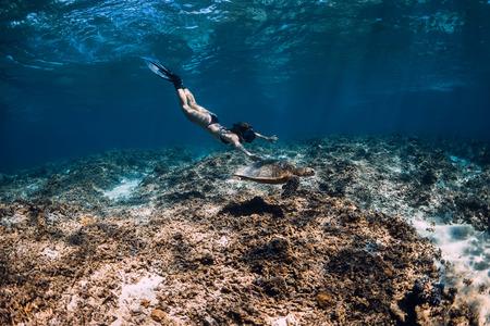 Woman freediver swim underwater with sea turtle.