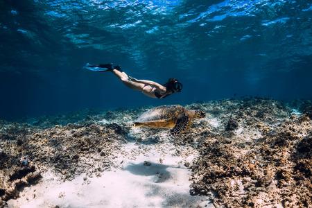 Woman freediver glides underwater with sea turtle.